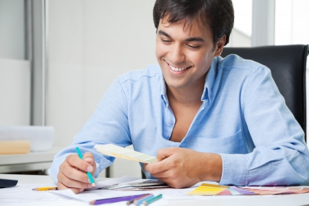 Happy young male interior designer looking at color swatches photo
