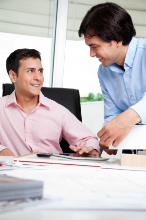 Young male architect looking at colleague while sitting in office chair Stock Photo - 15190426