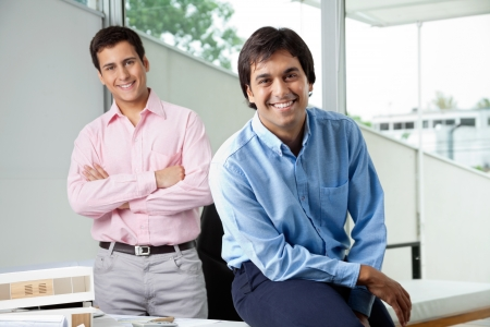 Portrait of young male architect smiling while colleague stands with arms crossed in background photo