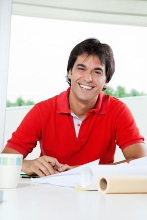 Portrait of happy young male architect working on blueprints at desk photo