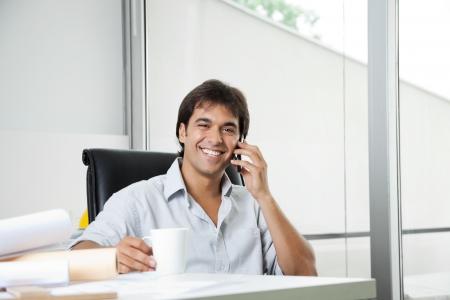 answering phone: Retrato de la alegre joven llamada telef�nica macho arquitecto contestador mientras tomando un caf� Foto de archivo