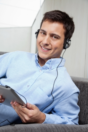 Portrait of handsome young man in formal shirt listening to music on digital tablet photo