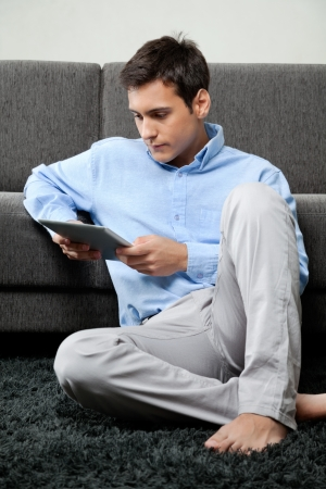 adult magazines: Young man in formal wear looking down at digital tablet while sitting on rug at home