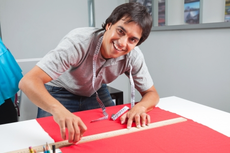 Portrait of young male dressmaker measuring a red fabric with ruler on table photo
