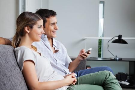 aire acondicionado: Hombre que sostiene el mando a distancia mientras se est� sentado con su novia en casa