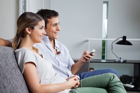 Man holding remote control while sitting with girlfriend at home photo