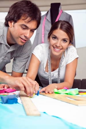 Portrait of young female fashion designer smiling while coworker draws line on fabric with chalk Stock Photo - 15190570