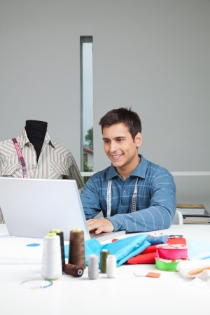 Happy male tailor using laptop while sitting by table with dressmaking accessories Stock Photo - 15190361