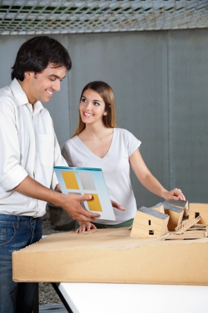 tangible: Young male architect looking at model house while female colleague smiling at him
