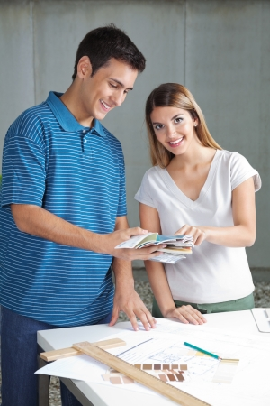 Portrait of young female architect with colleague choosing color from the swatches Stock Photo - 15205624