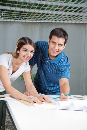 Portrait of young architects working on blueprints together Stock Photo - 15190582