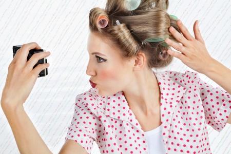 estereotipo: Mujer joven con rulos puckering mientras toma un retrato de uno mismo a través de una cámara de la vendimia Foto de archivo