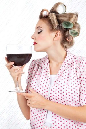 Young woman with hair curlers having giant glass of red wine photo