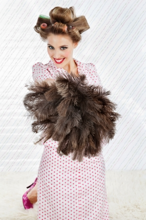 Portrait of happy young woman with hair curlers holding an ostrich feather duster photo