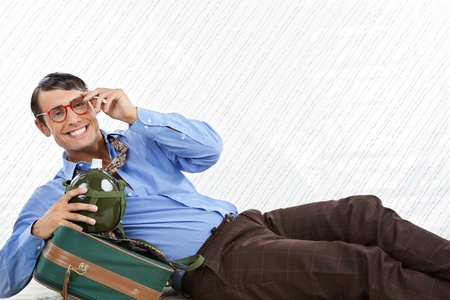 Portrait of happy geek businessman lying down with travel bag on textured background Stock Photo - 15190984