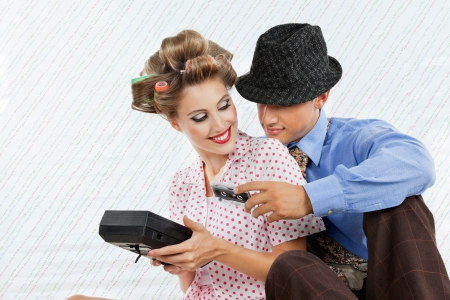 hair curler: Retro styled young couple holding an old fashioned cassette player over textured background
