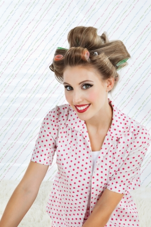 Portrait of an attractive young woman smiling with curlers in hair Stock Photo - 15191028