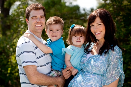Outdoor portrait of a happy young family with pregnant mother photo