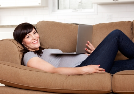 Relaxed happy pregnant woman sitting on sofa with laptop computer photo
