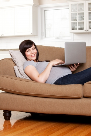 Happy pregnant woman using computer in living room photo