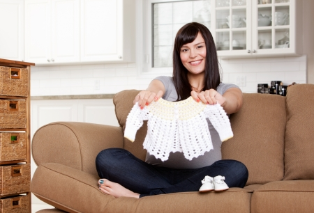 Portrait of expecting mother holding up knitted sweater photo