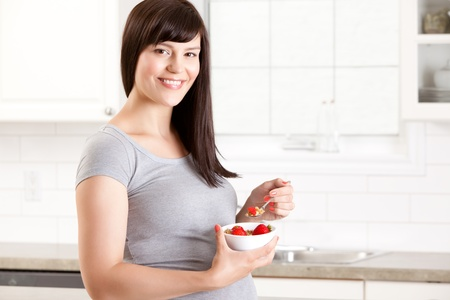 Portrait of a pregnant happy woman eating a healthy meal in kitchen at home Stock Photo - 15205388