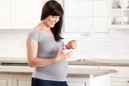 Happy pregnant woman in kitchen eating a healthy snack of strawberries and granola Stock Photo - 15205440