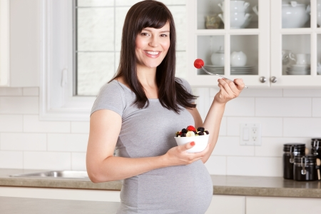 Pregnant woman eating a healthy snack at home in kitchen Stock Photo - 15205276
