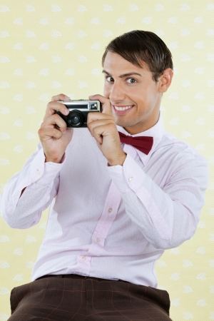Portrait of male geek photographing through a retro camera over textured background Stock Photo - 15191002