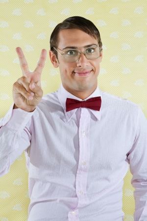 Portrait of male geek gesturing peace sign over yellow textured background photo