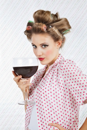 hair roller: Portrait of beautiful young female with hair curlers holding giant glass of wine