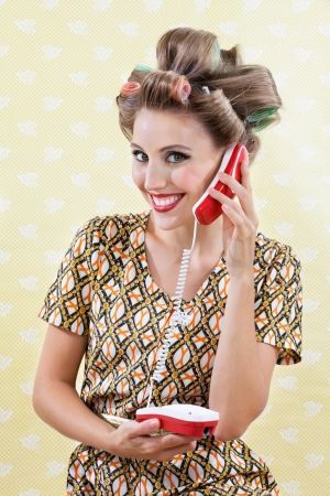 call girl: Portrait of an attractive young woman with hair curlers holding toy phone over a textured background Stock Photo