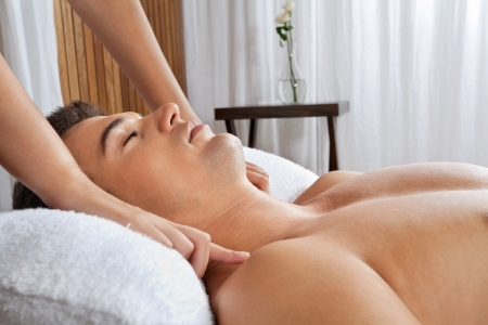 eye massage: Young shirtless man receiving massage from masseur at health spa