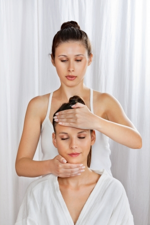 Female masseuse giving a head massage to woman at health spa Stock Photo - 15205298