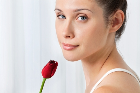 Portrait of pretty young female with red rose over white background Stock Photo - 15205294