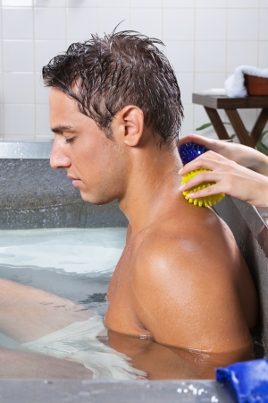 Side view of young man in pool receiving back massage with stress ball by a female Stock Photo - 15190740