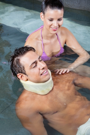 Young man wearing neck brace in pool with beautiful woman photo