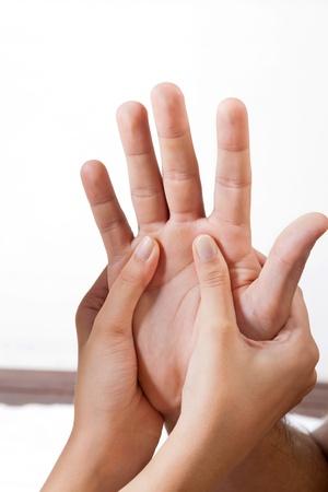 reflexologie plantaire: Gros plan de femme main de donner un traitement d'acupression de palme pour homme