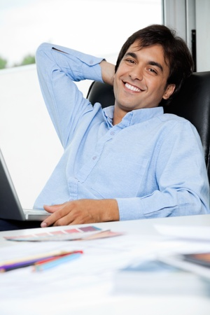 designer chair: Portrait of relaxed young male interior designer with laptop sitting in office chair Stock Photo