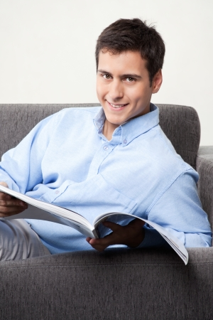 adult magazines: Young man holding magazine on couch
