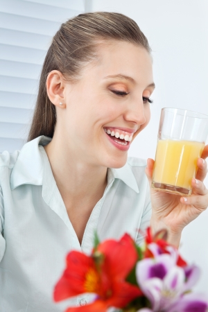vertical wellness: Happy young businesswoman holding glass of orange juice