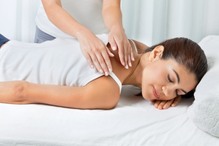 Young woman relaxing with eyes closed as she is receiving back massage by female masseuse Stock Photo - 14937769