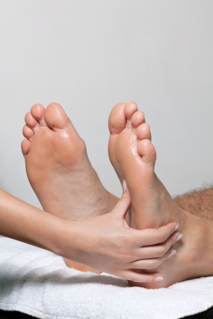 Feet being massaged by female masseuse on white towel photo