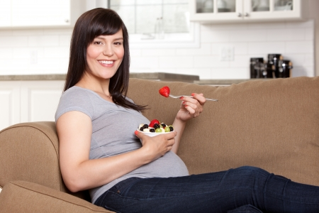 woman eat: Happy pregnant woman sitting on sofa eating bowl of fresh fruit Stock Photo