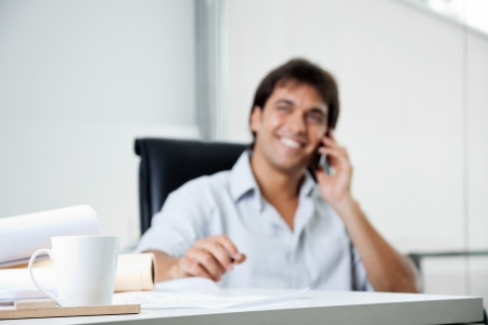 businessman phone: Focus on coffee cup with male architect answering phone call in background
