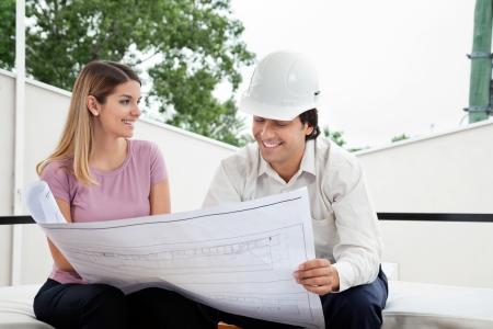 Young female client discussing house plan with male architect photo