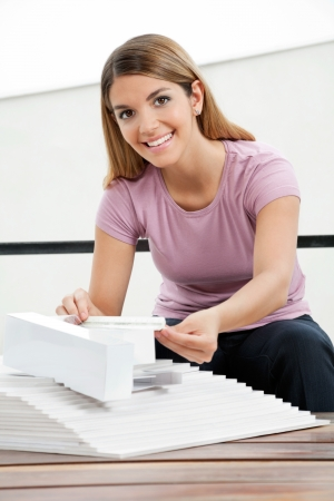 tangible: Portrait of beautiful female architect working on a tangible model