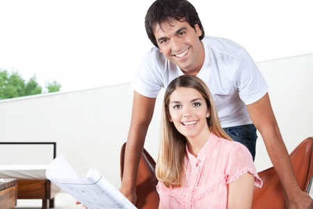 Portrait of young couple with blueprints  photo