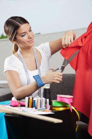 Young female fashion designer cutting a red fabric with dressmaking accessories on table photo