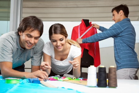 dressmaker: Tailors working together with colleague measuring red fabric on mannequin in background Stock Photo